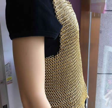 A person is wearing a piece of copper plating chainmail shirt without sleeves.