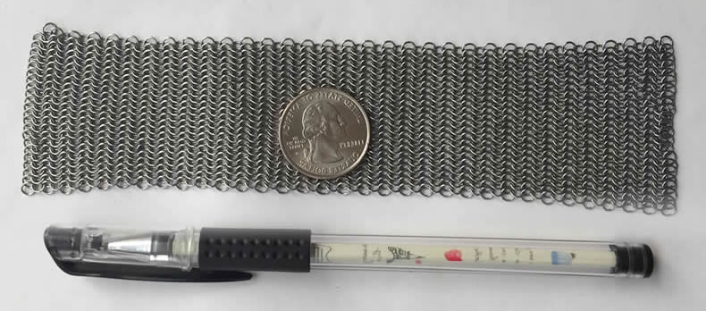 A piece of silver white stainless steel chainmail sheet is made of small rings with coin on it and pen beside it.