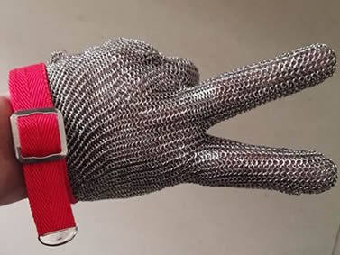 A hand is wearing a piece of stainless steel chainmail glove with silver white metal buckle.