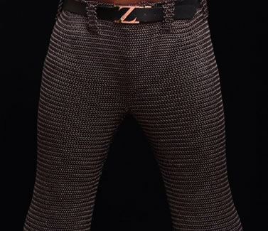 A person is wearing a pair of dark brown chainmail chausses with a black belt.