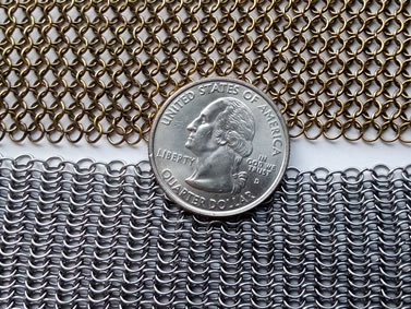 Two pieces of chainmail sheet with a metal coil in the middle: brass chainmail sheet and mild steel chainmail sheet.