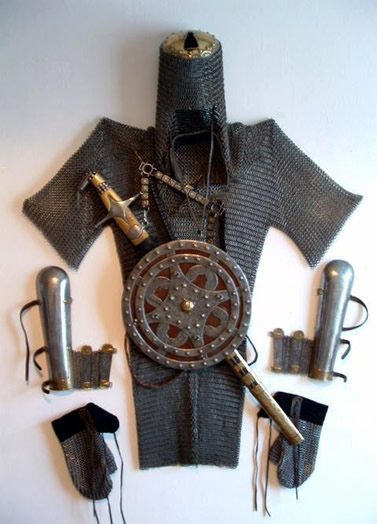 Black chainmail shirt, chainmail coif, chainmail gloves, sword and shield are hung on the wall.