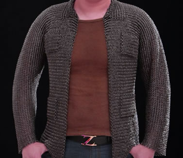 A person is wearing a piece of dark brown chainmail shirt with two hands in pockets.