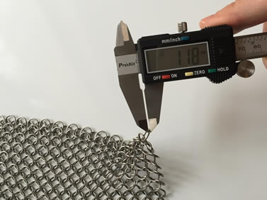 A piece of sliver white chainmail armor and the wire diameter of a ring is being measured by a caliper.