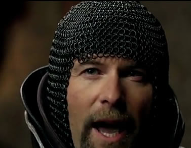 A man wearing a black chainmail coif in a movie is speaking.