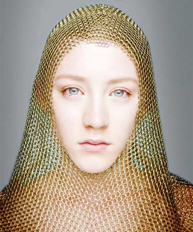 A woman is wearing a golden color chainmail coif.