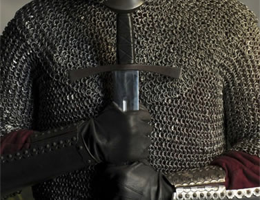 A man wearing a stainless steel chainmail shirt and chainmail collar is holding a sword.