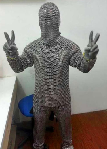 A person is wearing a complete set of silver white chainmail armor with 2 hands making the gesture of victory.