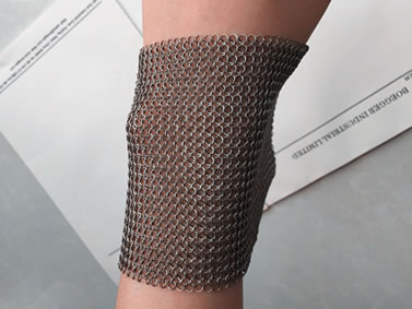 A piece of stainless steel chainmail sheet is on a wrist.