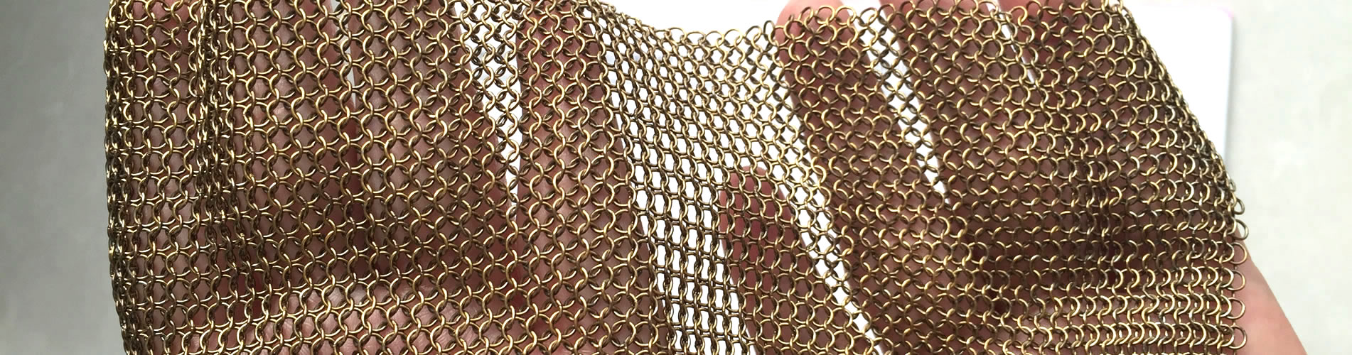A piece of copper plating chainmail is spread out on two hands.