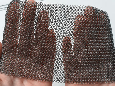 Two hands are holding a piece of aluminum chainmail sheet.