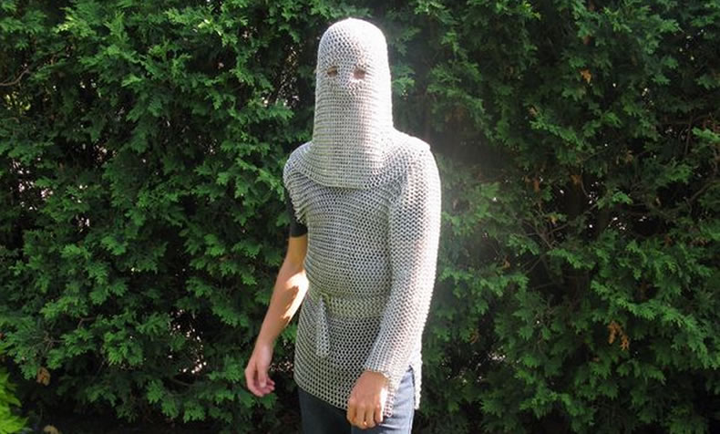 In front of green plants, a person is wearing a silver white chainmail coif and a chainmail shirt.