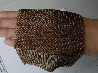 A piece of brass chainmail is on the back of the hand in stretching style.