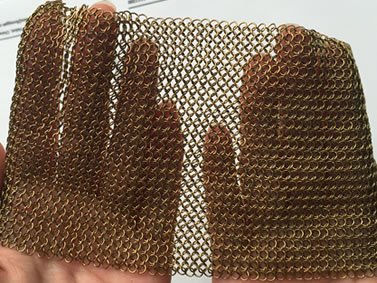 Two hands are holding a piece of brass chainmail sheet.