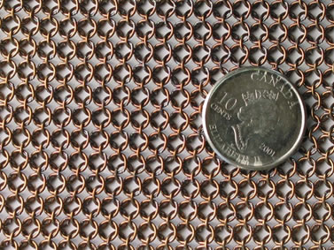 A piece of copper plating round butted chainmail shirt with a metal coin on it.