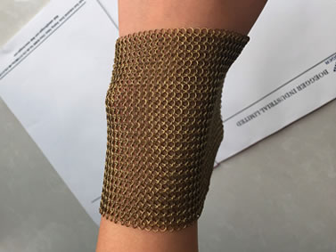 A piece of brass chainmail sheet is on a wrist.