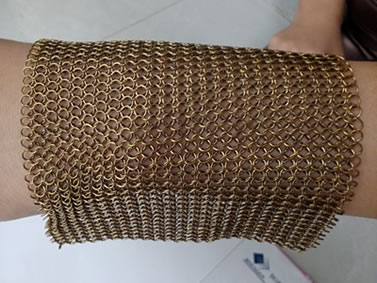 A piece of brass chainmail is on the wrist in stretching style.
